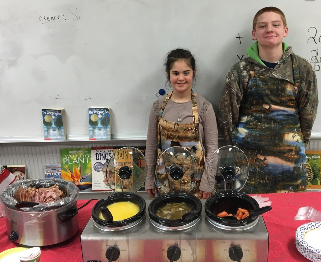 boy and girl wearing aprons in front of crockpots