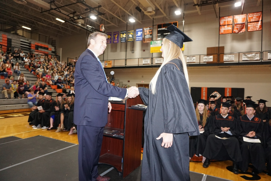 graduate shaking a man in a suit's hand