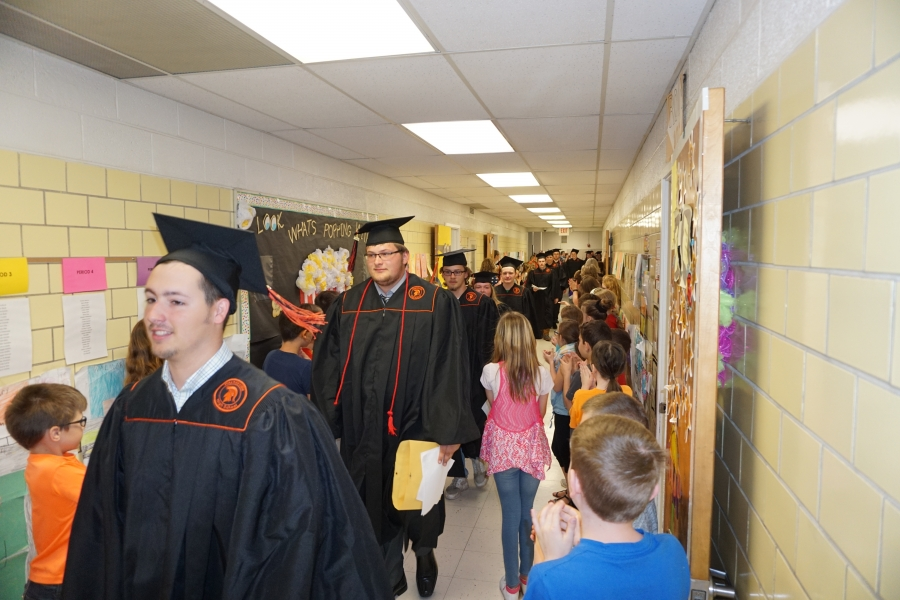 graduates walking past small children