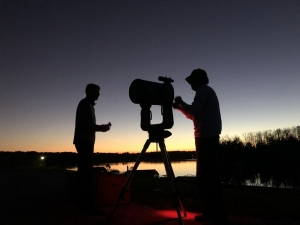 silhouette of two people at a camera