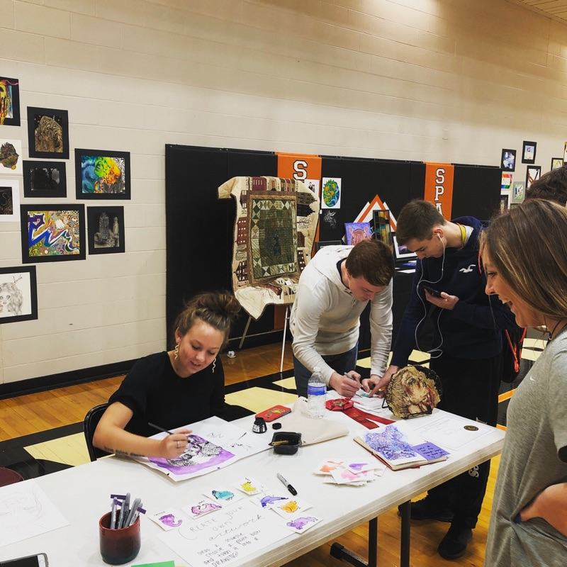 students working on art pieces at a table