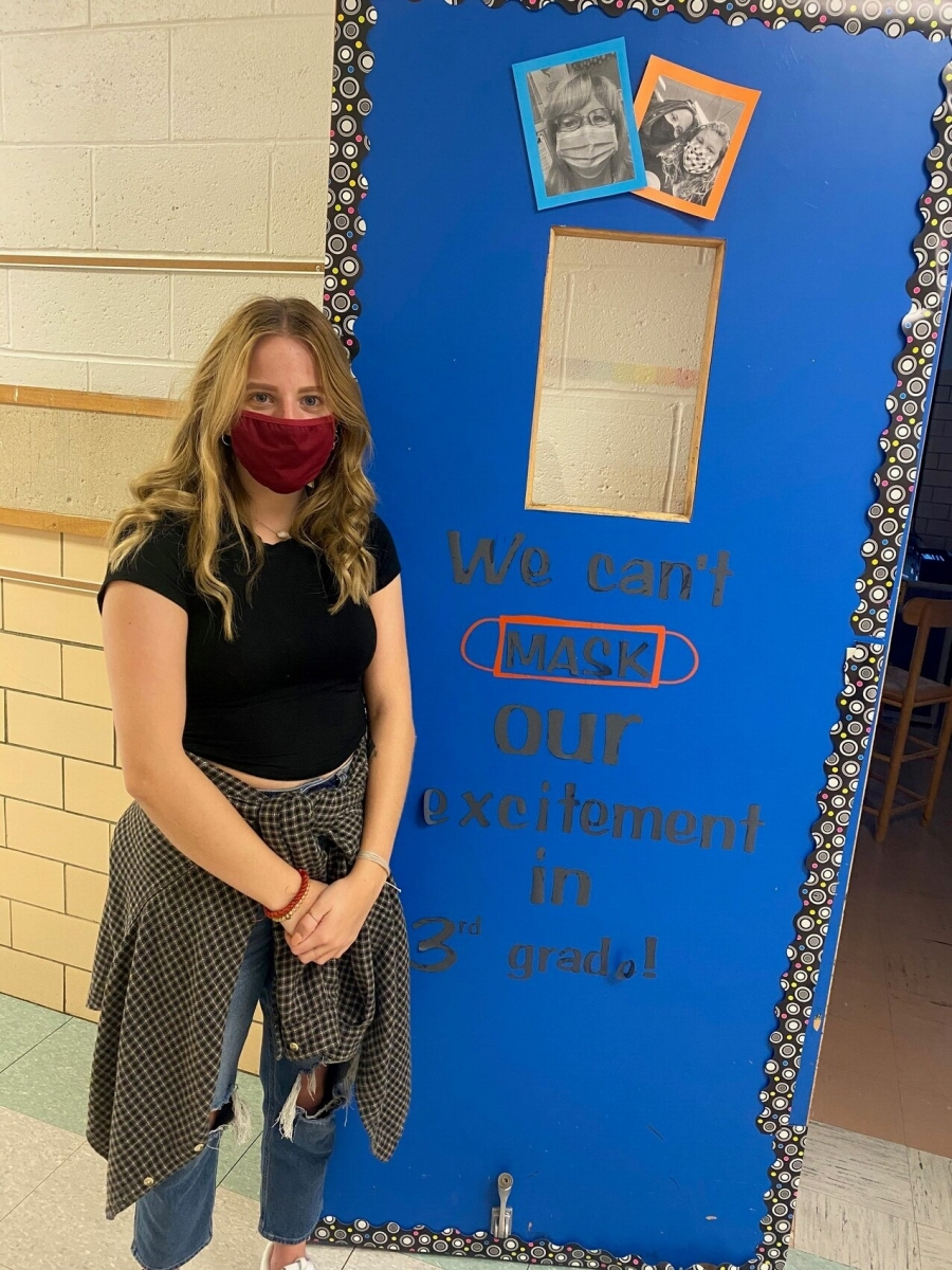 girl wearing a mask in front of a blue door