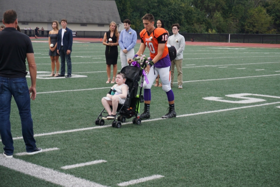 boy in football uniform pushing a stroller