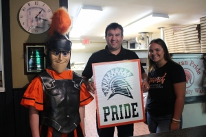 spartan mascot and three people holding a sign