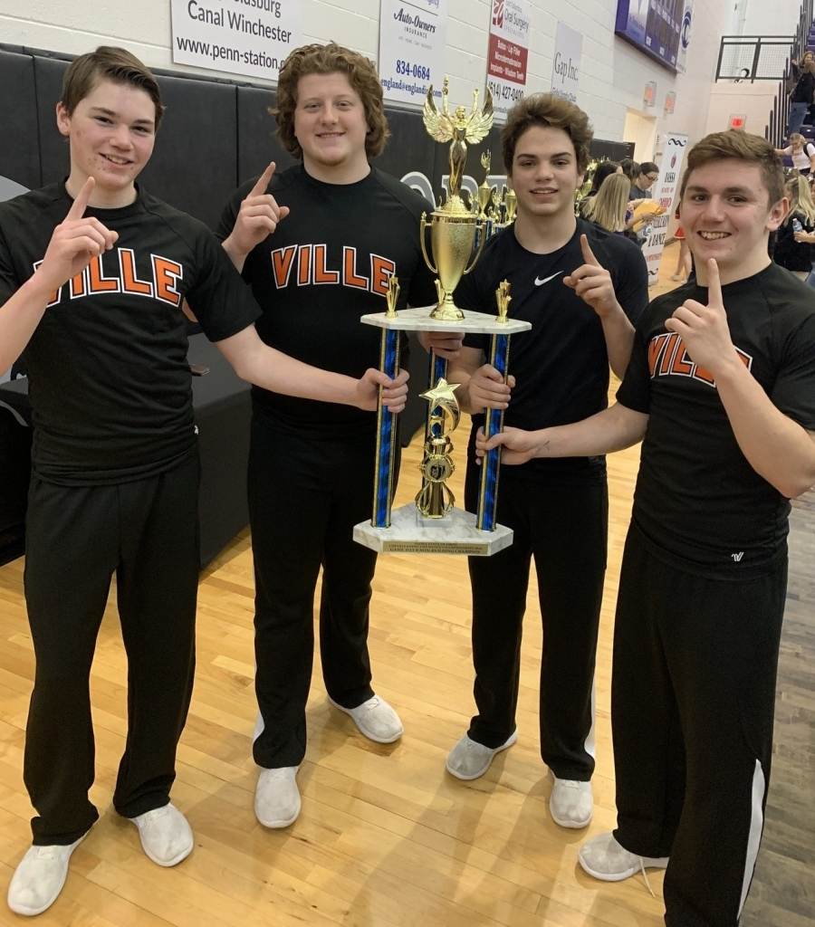 four male cheerleaders holding a trophy