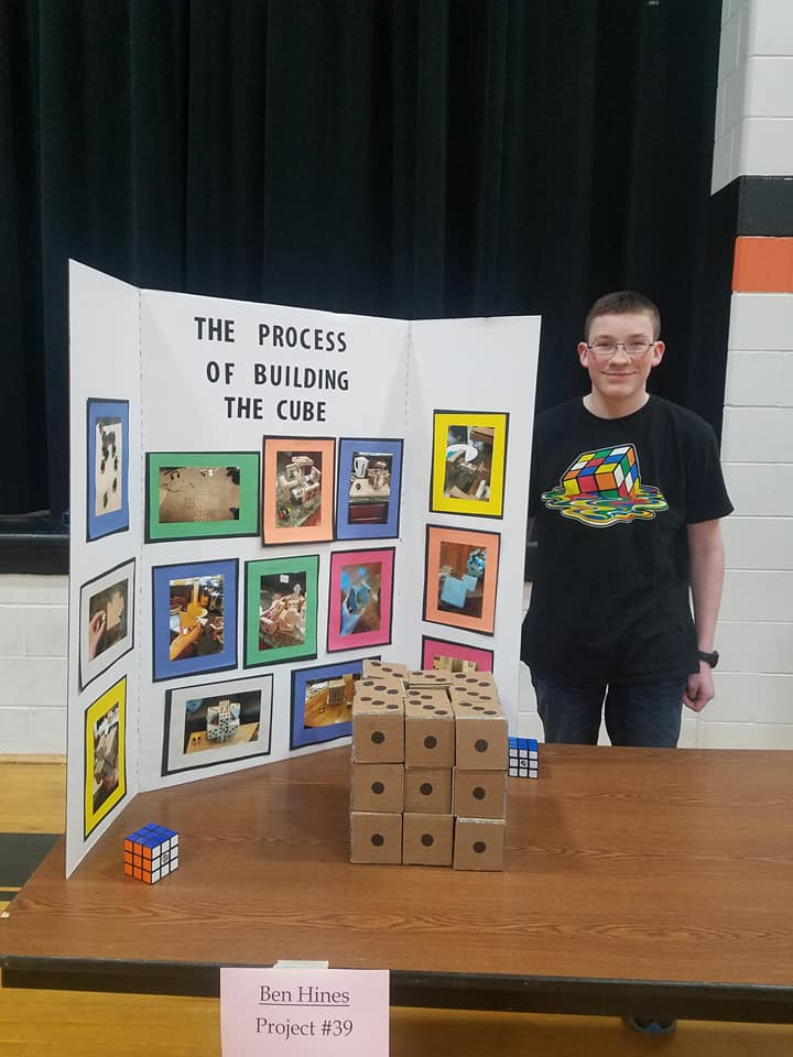 boy standing in front of a cardboard display