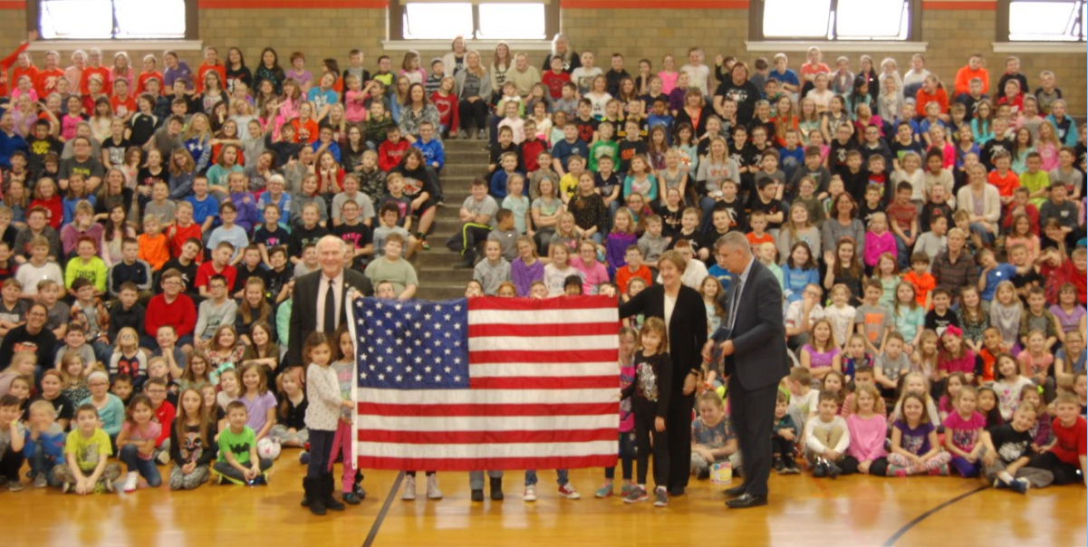 people holding a flag in a gymnasium full of students