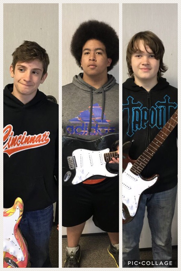 image of three boys holding guitars