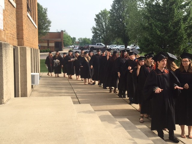 graduates in a line outside a building