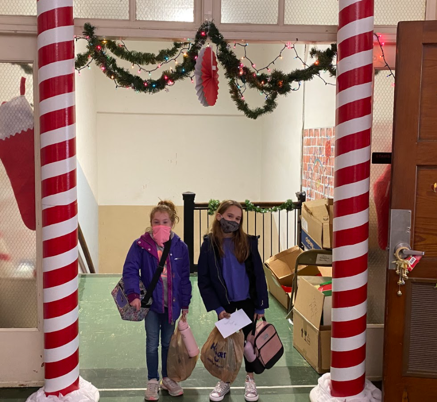 two girls with bags inside candy cane poles