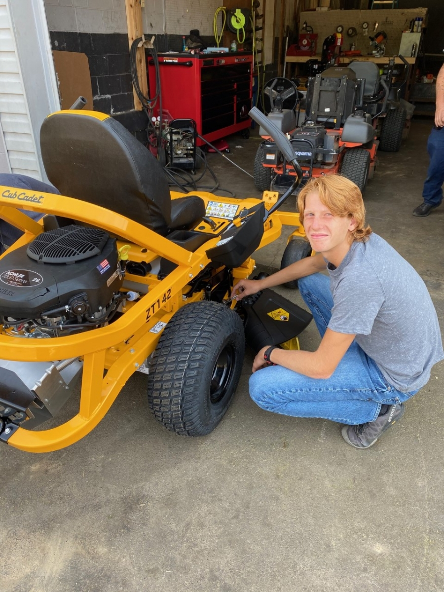 person working on a riding mower