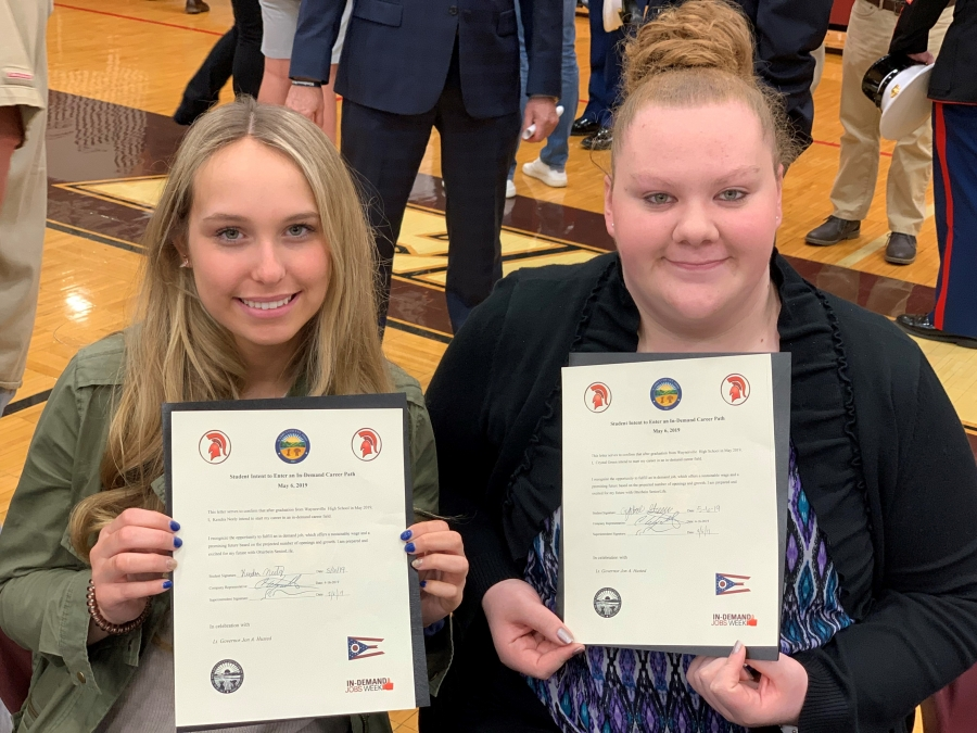 two girls holding certificates