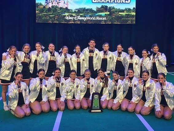 team all wearing white jackets and biting medals