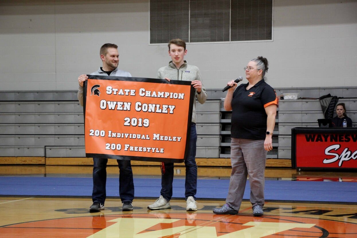 three people and a banner