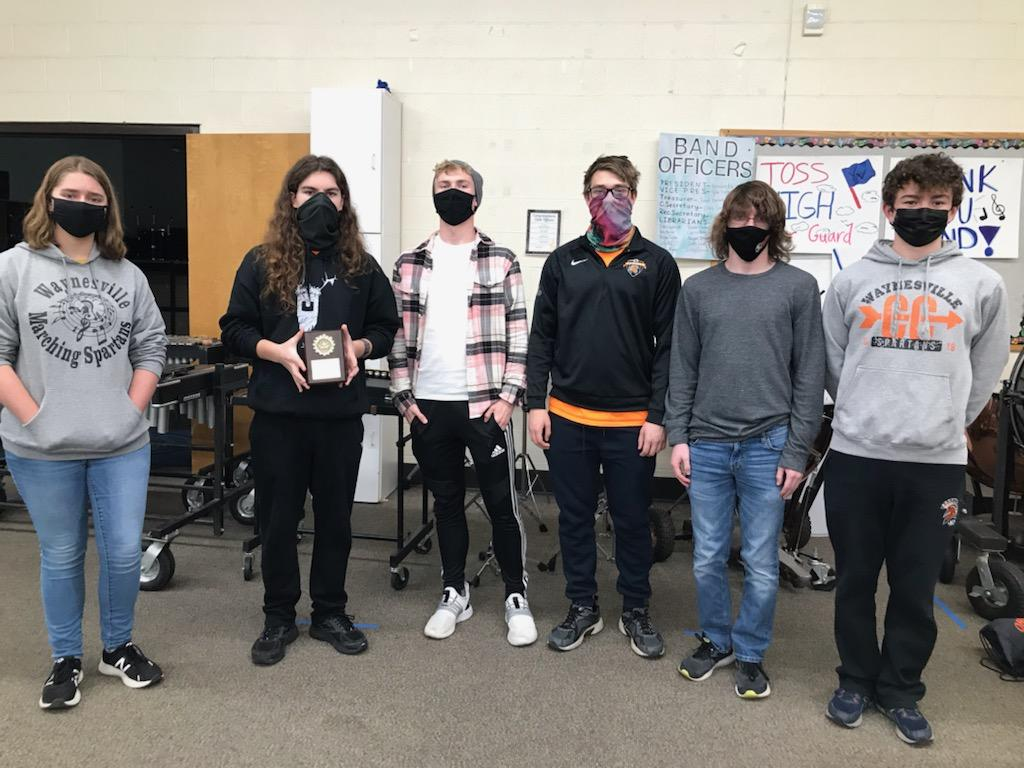 6 people wearing masks and one holding an award