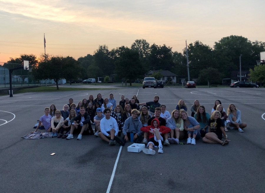 people sitting in parking lot with sunrise behind them