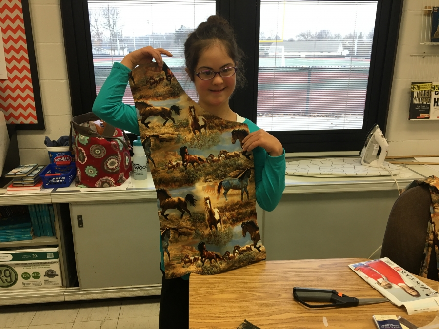 girl holding a cut pattern of fabric