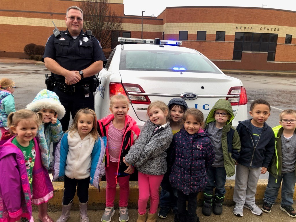 officer and little kids in front of police car