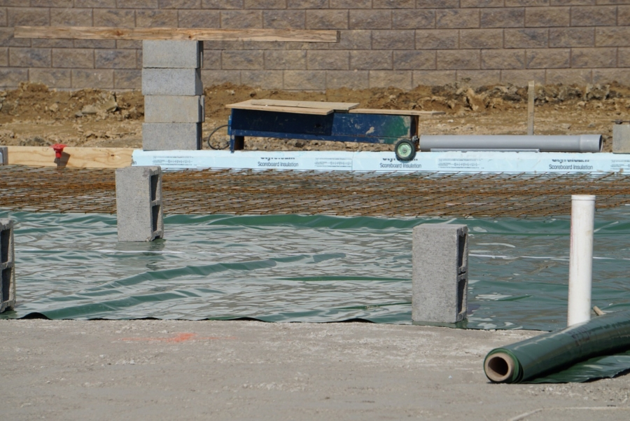 blue plastic sheets cover a foundation